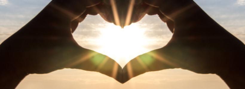 2 Hände bilden ein Herz vor dem Sonnenuntergang